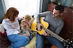 Husband & wife entertaining child