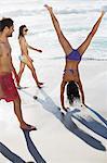 Friends watching woman in bikini doing handstand on beach