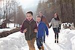 Happy family running in snowy lane