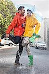 Happy couple in wellingtons splashing in rainy street