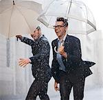 Happy businessmen with umbrellas walking in rain