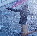 Businesswoman dancing in rain