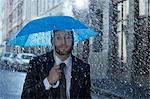 Portrait of businessman with tiny umbrella in rain