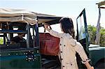 Woman putting handbag in SUV