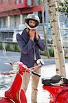 Man standing near a scooter on a street