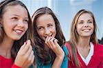 Close-up of three girls eating grapes