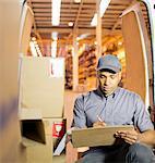Delivery boy using clipboard in van