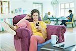 Man listening to headphones in armchair
