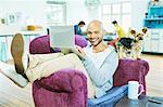 Man using laptop in armchair