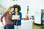 Women using tablet computer in kitchen