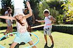 Children hula hooping in backyard