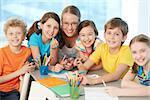 Portrait of joyful schoolkids and successful teacher looking at camera