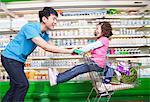 Father Pushing Daughter in Shopping Cart Inside Supermarket, Laughing