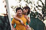 Boyfriend holding his girlfriend next to the tennis net
