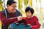 Grandfather and grandson looking at fishing tackle box