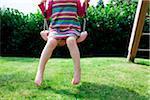 Girl sitting on a swing in backyard