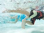 USA, Utah, Orem, Boy (4-5) and girl (2-3) swimming in pool