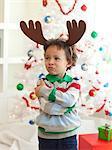 Happy young boy deer horns standing  in front of Christmas tree