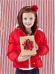 Studio portrait of girl (4-5) holding of Christmas gift