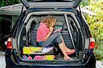 Teen girl with luggage in car