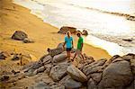 Couple with dog hiking on beach rocks
