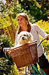 Teen girl on bike with dog in basket
