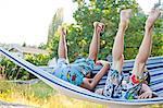 Children playing in hammock on beach