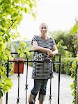 Woman standing by garden gate