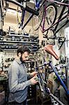 Mid adult repairman working at bicycle repair shop
