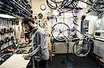 Profile shot of mid adult repairman working at bicycle repair shop