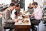 Businessmen and businesswomen having breakfast together in office restaurant