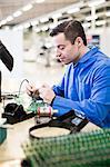 Mature male technician soldering circuit board at desk in industry
