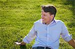 Businessman Sitting In Grass, Munich, Bavaria, Germany