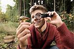 Teenage boy looking at mushroom through magnifying glass, Bavaria, Germany, Europe