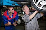 Car mechanics discussing and analyzing car repair