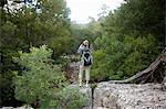 Teenage hiker taking photographs from rocks