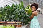 Girl watering plants in greenhouse