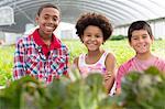Portrait of three children in plant nursery