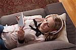 Girls lying on sofa using digital tablet