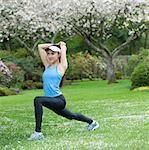 Teenage girl wearing blue sportswear stretching in park