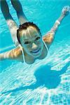 Woman wearing white bikini swimming in pool, underwater view, portrait