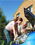 Senior man and teenage girl (15-17) looking under car bonnet, outdoors