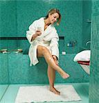 Mature woman sitting on edge of bath applying cream to leg