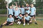 Sport team of children (5-9) celebrating beneath goal
