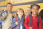 Group of children (6-9) standing by school bus, portrait