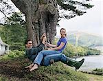 Woman sitting on man's lap on swing, smiling