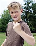 Boy (9-11) in park, grimacing, raised fist, portrait