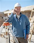 Surveyor wearing hard hat using mobile phone on site