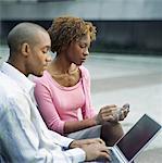 Business couple outdoors, man using laptop woman using palmtop