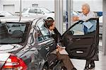 Mature salesman talking to man sitting in car in showroom